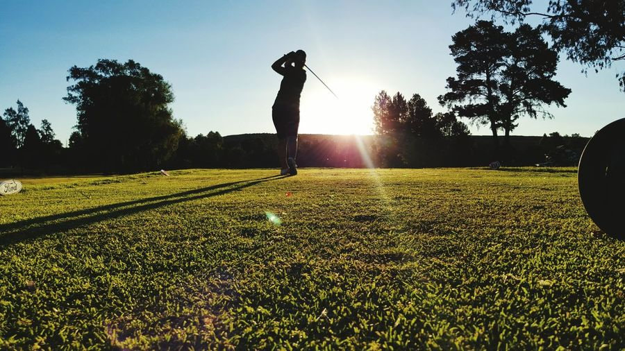 Silhouette person playing golf against clear sky