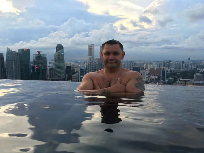 Portrait of man in infinity pool against city