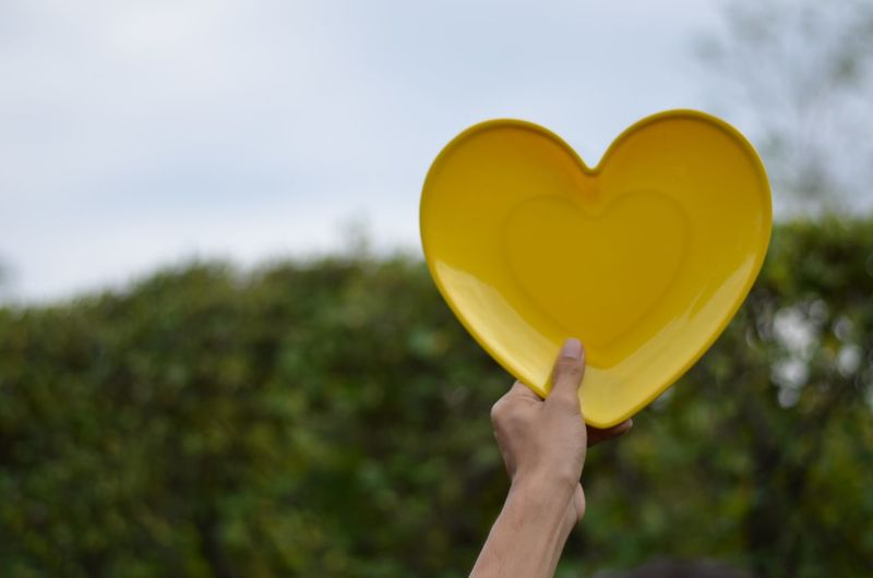 Cropped image of person holding heart shaped plate outdoors