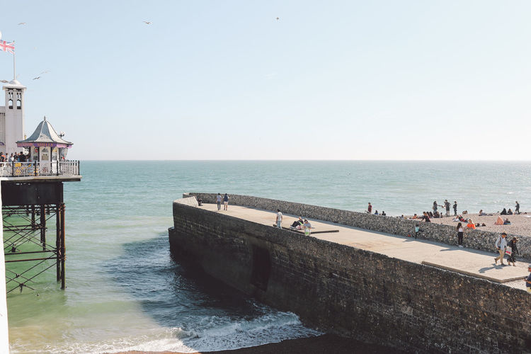 People On Pier On Sea Against Clear Sky