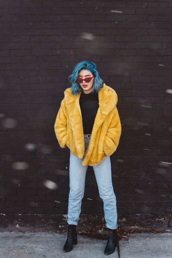 Young Women Yellow Wall - Building Feature Snow Jacket Real People Lifestyles Portrait Looking At Camera Standing Leisure Activity Full Length Front View Young Adult Cold Temperature Clothing Winter Fashion Hood - Clothing One Person Warm Clothing Scarf Outdoors Beautiful Woman Fashion