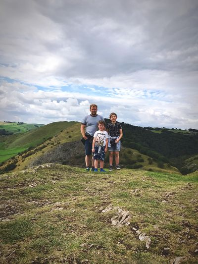 Full length of father and kids standing on mountain against sky