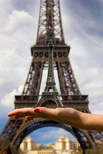 Cropped hand holding replica eiffel tower against eiffel tower in paris
