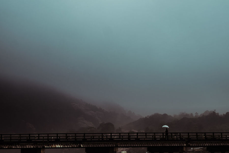 lonely person with an umbrella crossing a bridge in fog and rain Architecture Beauty In Nature Bridge Bridge - Man Made Structure Built Structure Connection Fog Lonely Lonely Person Mountain Nature Outdoors Railing Rain River Road Scenics Sky Tranquility Transportation Umbrella Weather