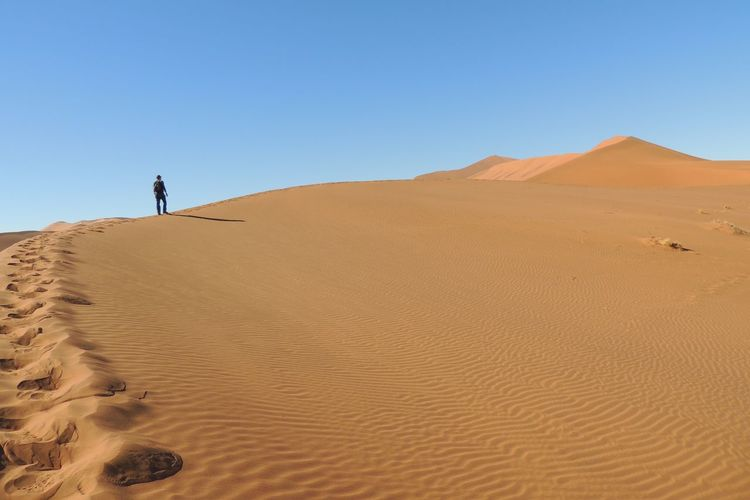 Low angle view of man walking at desert against clear blue sky