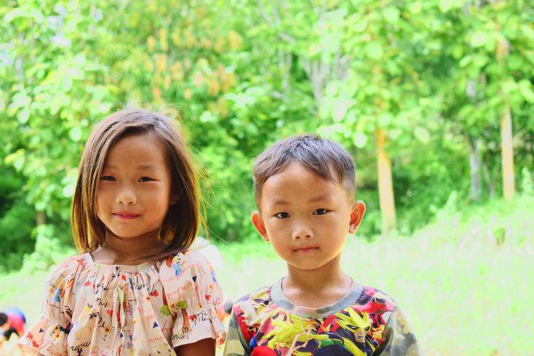 Portrait of cute siblings against trees in park