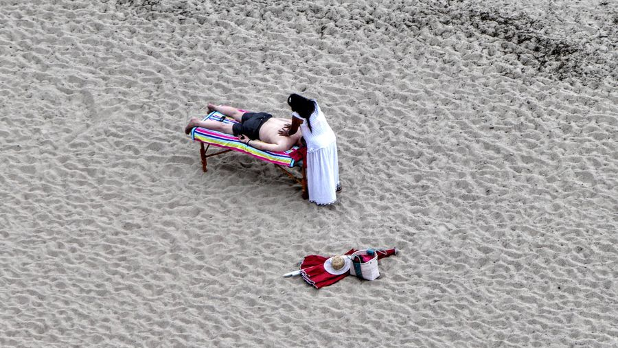 High Angle View Of Woman Giving Massage To Man At Sandy Beach