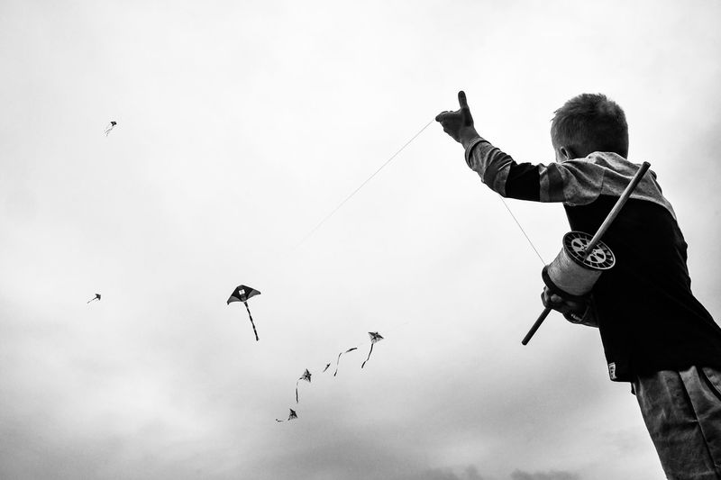 Low angle view of boy flying kite against sky