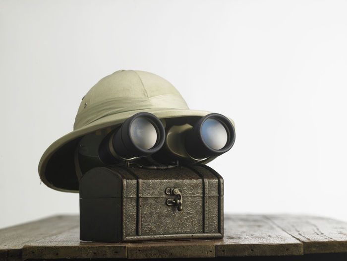 Old colonial hat with a pair of binoculars on wooden table Box Exploring Hat Hiking Hunter Treasure Box Accessories Binoculars Chest Colonial Discovery Equipment Explorer Gear Hardhat  Helmet Object Protection Surprise Surveillance Treasure Chest Treasure Hunting Trunk Vintage Vision