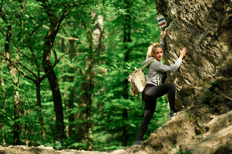 Side View Of Young Woman With Backpack Climbing Tree In Forest