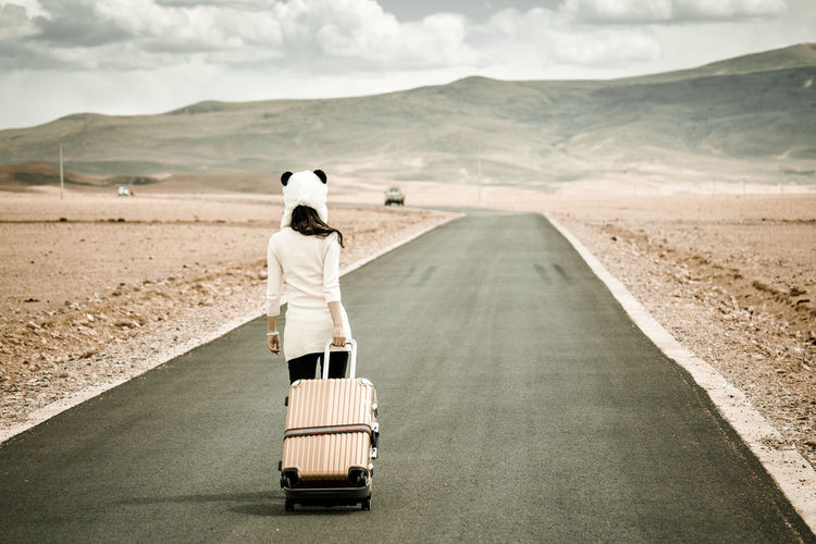 Girl taking a road trip Adult Adventure Baggage Desert Dream Freedom Girl Journey Lifestyle Lonely Luggage One Person Outdoors People Rear View Retro Road Suitcase Travel Traveler Trip Vacations Vintage Way Woman