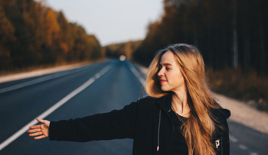 Portrait of young woman standing on road