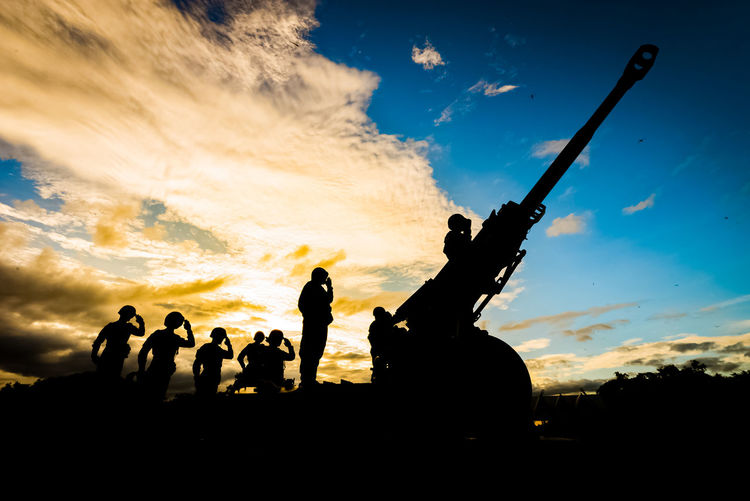Silhouette Soldiers Saluting By Cannon Against Sky During Sunset