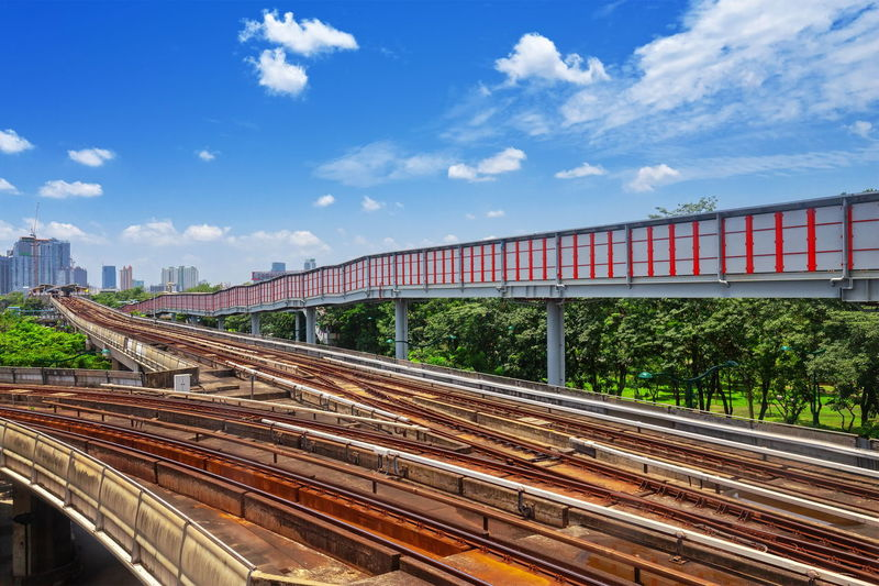 Railroad tracks in city against sky