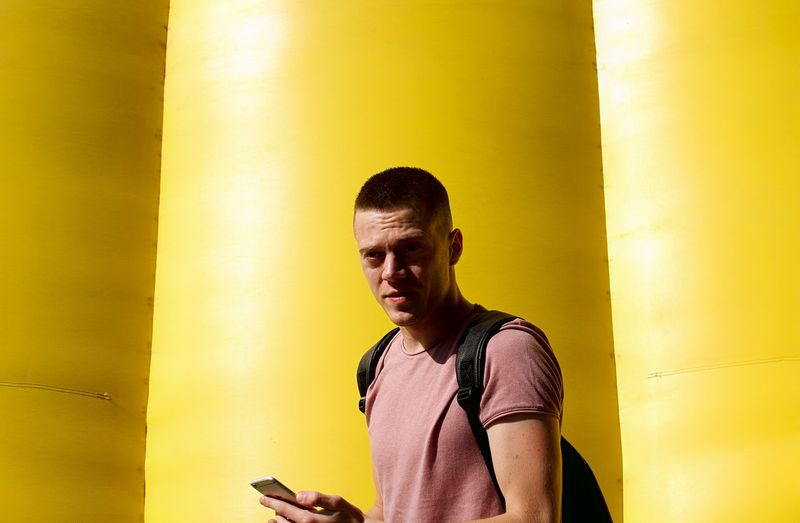 Portrait Of Man Using Mobile Phone By Yellow Wall