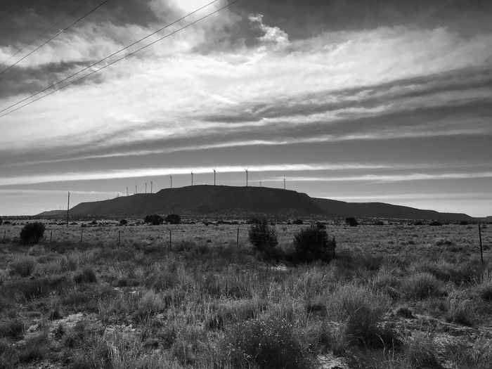 """King's Of The Mountain"" A windmill power farm atop a high plateau that rises above the grasslands of Central New Mexico. Plateau New Mexico Skies New Mexico Photography Windmill Farm Windmills Grasslands Blackandwhite Photography Black & White Blackandwhite Sky Grass Field Landscape Nature No People Cloud - Sky Scenics"