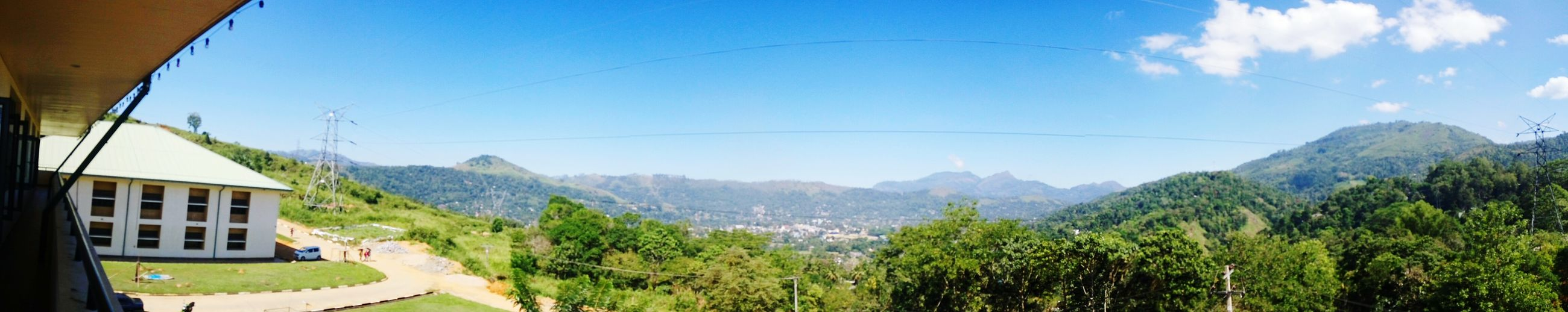 mountain, mountain range, sky, scenics, tranquility, tranquil scene, landscape, tree, blue, beauty in nature, nature, green color, power line, non-urban scene, day, idyllic, sunlight, outdoors, built structure, cloud