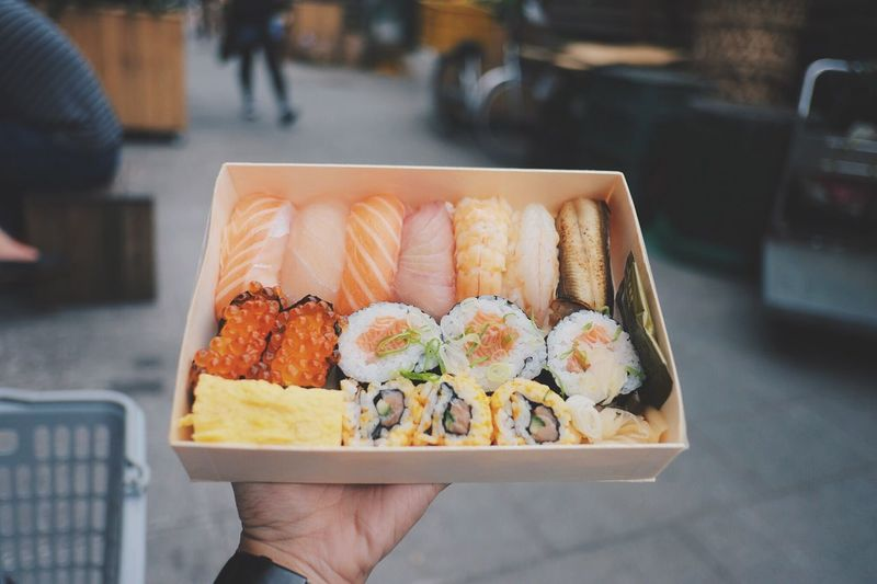 Cropped hand of man holding sushi in container