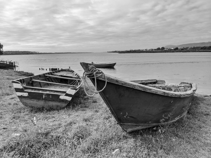 Boats moored at shore against sky