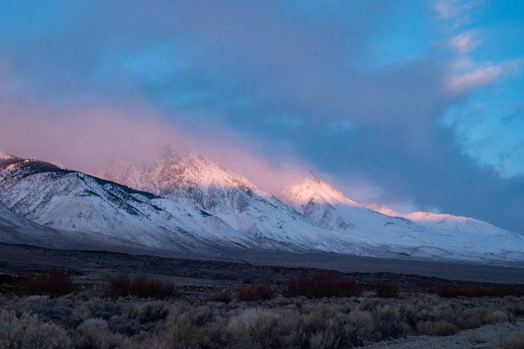 cloudy sunrise morning sky above snowy mountain peaks Sierra Nevadas California USA Sky Beauty In Nature Mountain Scenics - Nature Tranquility Cloud - Sky Landscape Mountain Range Environment Nature Sunset No People Winter Cold Temperature Snowcapped Mountain Sierra Nevada Mountains California Sunrise