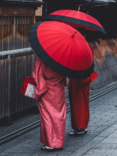 Rear view of person with umbrella walking on street during rainy season