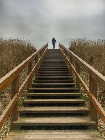 A woman standing on top of a wooden stairway in St. Peter-Ording on a cloudy winter day Alone Frisia St. Peter Ording Travel Woman Beauty In Nature Day Dike Full Length Future Low Angle View Nature One Person Outdoors People Railing Real People Rear View Sky Staircase Standing Steps Steps And Staircases The Way Forward Tree