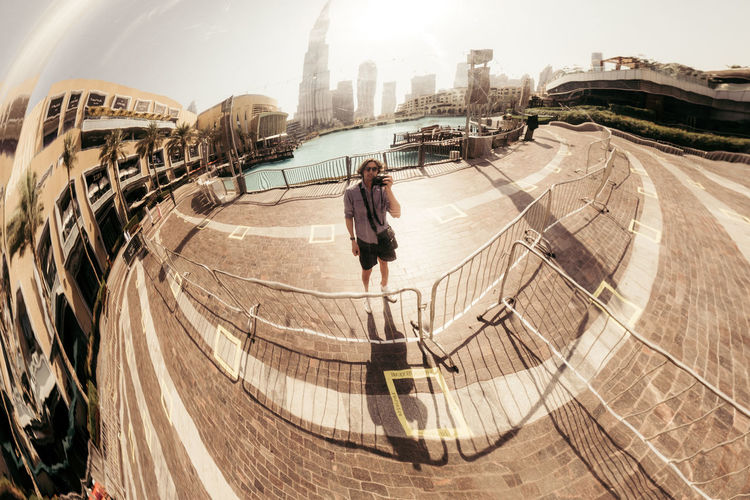 High angle view of woman standing by railing in city