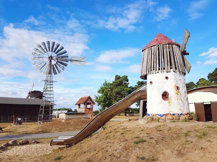 Traditional windmill on beach against sky