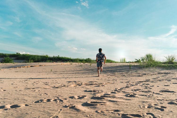 Full length rear view of man running on sand