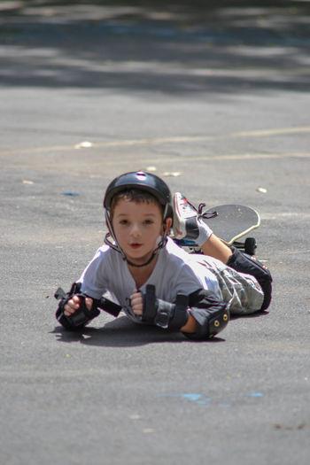 Full length portrait of boy lying down on road
