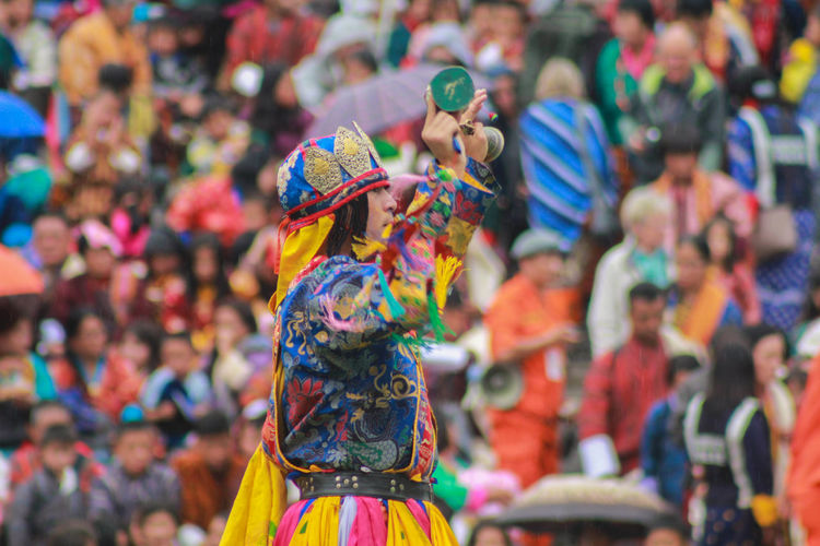 Side View Of Male Artist In Colorful Traditional Clothing Performing Against Audience
