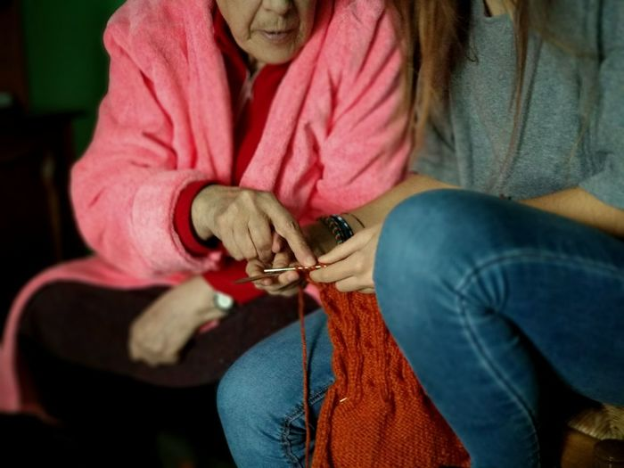 Midsection Of Mother Assisting Daughter In Knitting Wool At Home