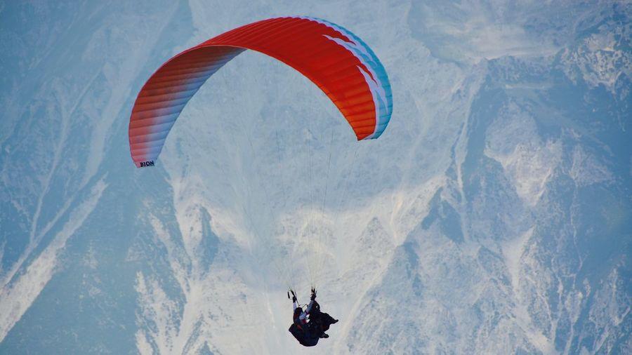 Person paragliding over mountain