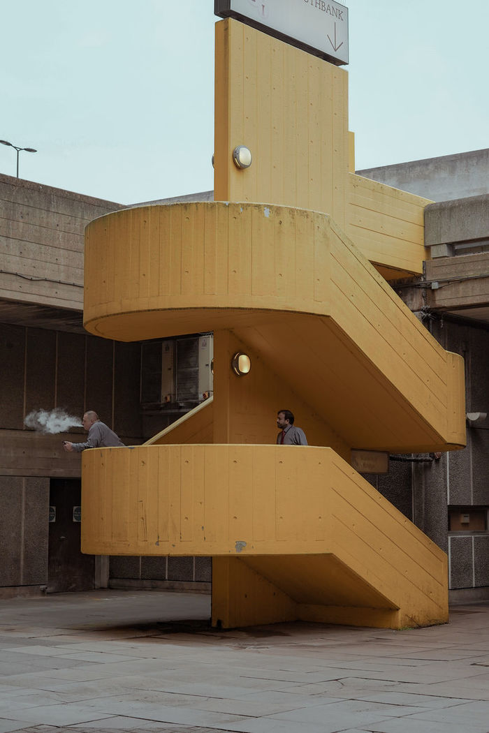 MAN BY YELLOW BUILDING IN CITY