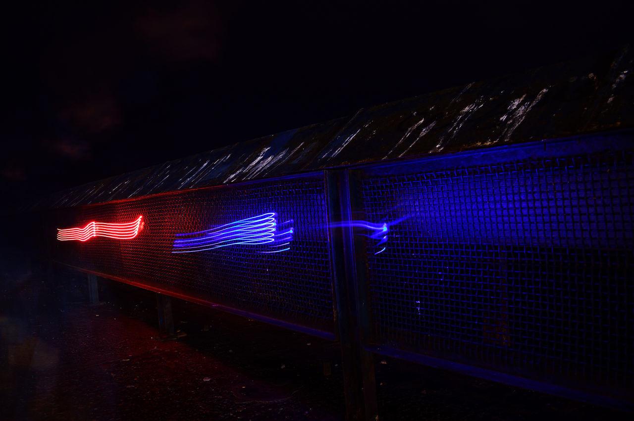 CLOSE-UP OF ILLUMINATED LIGHT TRAILS ON WALL