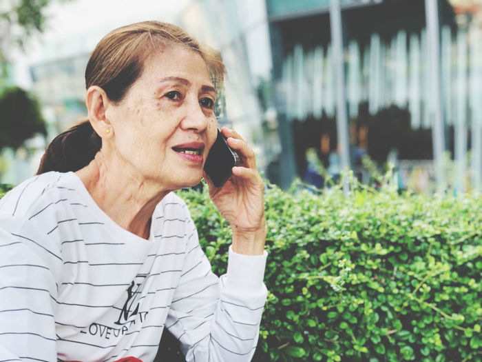 Portrait of mature woman talking on mobile phone at park