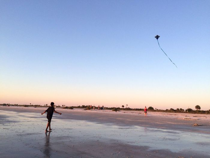 Man walking at beach against kite flying in clear sky during sunset