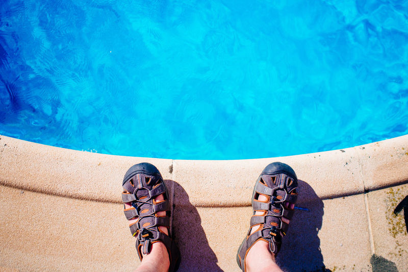 Low Section Of Man Standing At Poolside While Wearing Sandals