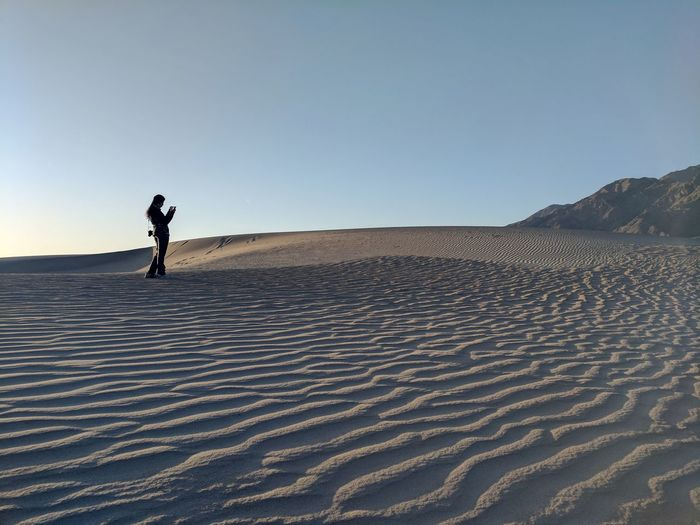 Mid distance view of woman standing at desert in death valley national park