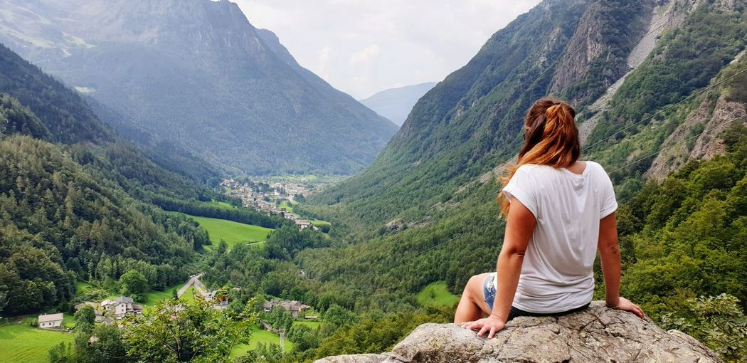 Rear view of woman sitting on rock while looking at mountains