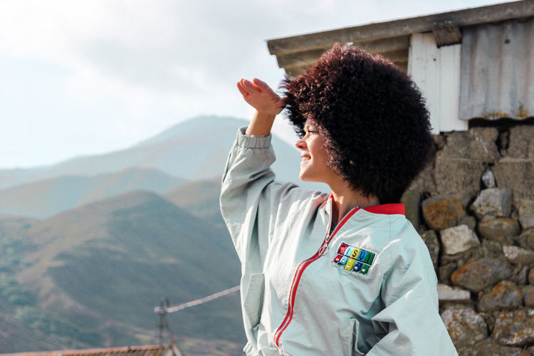 Afro woman shielding eyes while looking at view against mountains