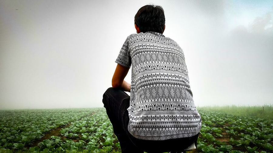 Rear view of mature man crouching on field against cloudy sky