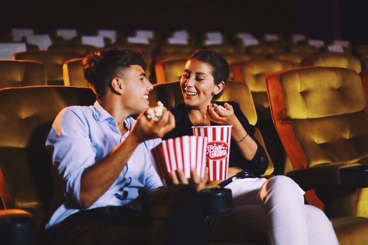 Happy couple with popcorn sitting in movie theater