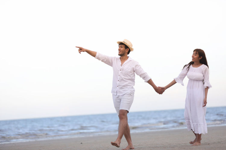 Man pointing while walking with woman at beach against sky