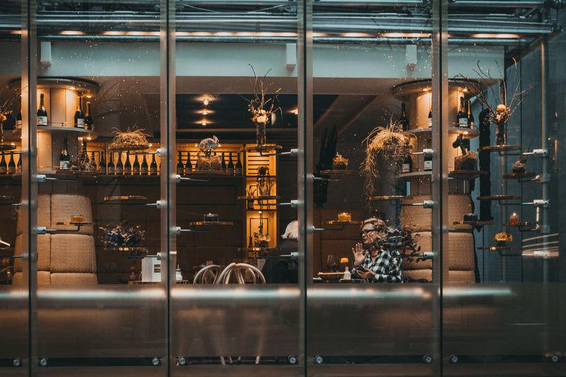 Illuminated restaurant at store seen through glass window