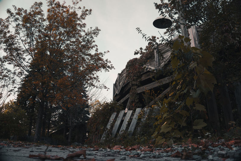Low angle view of abandoned building during autumn