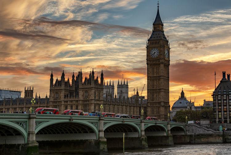 Westminster bridge over river against sky during sunset