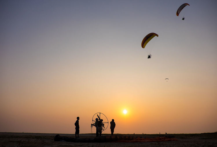Low Angle View Of Silhouette People Paragliding Over People At Beach During Sunset