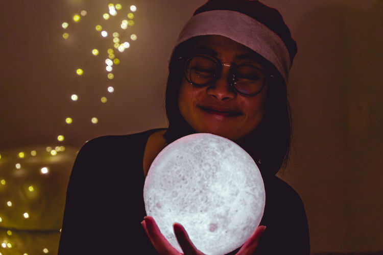 Smiling woman holding illuminated crystal ball