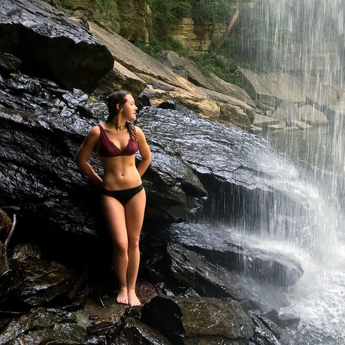 Full Length Of Young Woman In Bikini Standing By Waterfall